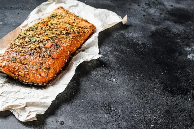 Zdrowa dieta wysokobiałkowa, wędzony atlantycki filet z łososia. pstrąg. czarne tło, widok z góry, miejsce na tekst
