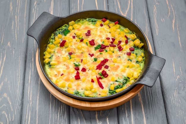 Zdrowa dieta. zapiekanka z ziemniakami, kukurydzą, zielonym groszkiem i szpinakiem i serem
