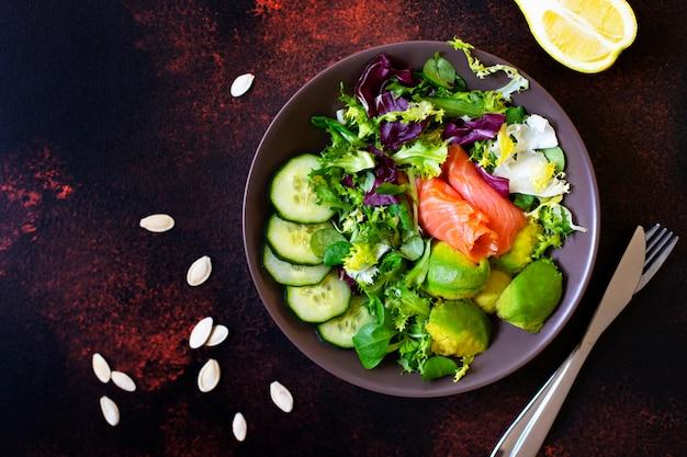 Zdrowa dietetyczna sałatka z łososiem, awokado, pestkami dyni, świeżymi warzywami i cytryną. pojęcie zdrowego odżywiania. ciemne tło, widok z góry, miejsce