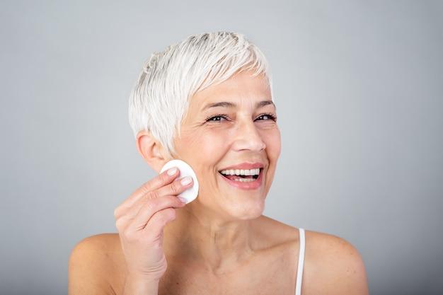 Zdrowa dojrzała kobieta usuwa makeup od jej twarzy z bawełnianym ochraniaczem odizolowywającym na szarym tle. piękno portret szczęśliwej kobiety cleaning skóra i patrzeć kamerę.