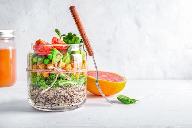 Zdrowa domowa sałatka w szklanym słoju z komosą ryżową, warzywami i ziołami om białym tle. koncepcja żywności wegańskiej.