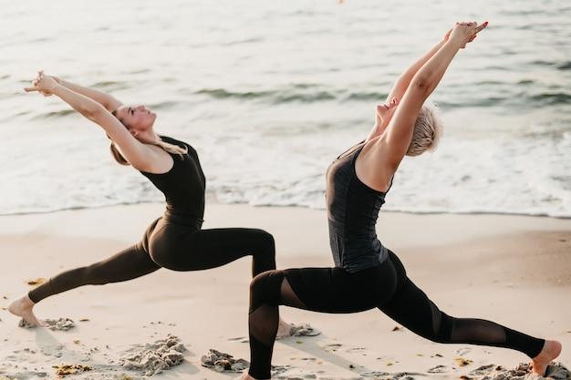 Zdrowa dysponowana kobieta ćwiczy joga z opiekunem fitness na plaży blisko oceanu