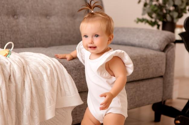 Zdrowa dziewczynka w pokoju obok szarej sofy uczy się chodzić