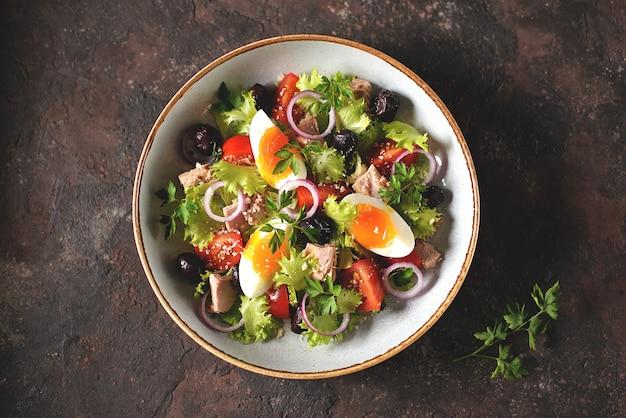 Zdrowa ekologiczna sałata z tuńczykiem z puszki, pomidorkami koktajlowymi, suszonymi oliwkami, czerwoną cebulą, jajkiem i parmezanem