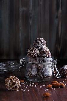 Zdrowa energetyczna granola gryzie w szklanym słoju z orzechami, daktylami, miodem i sezamem