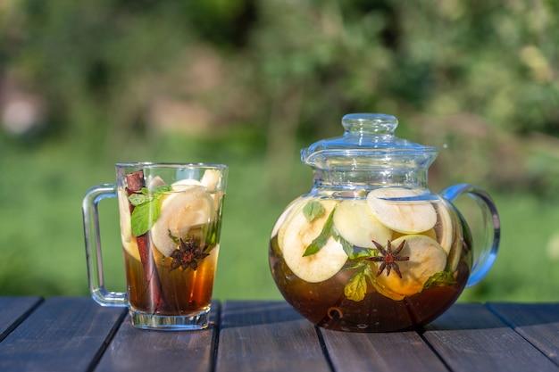 Zdrowa herbata jabłkowa w szklanym dzbanku do herbaty i kubek w letnim ogrodzie na drewnianym stole. bliska herbata jabłkowa z cynamonem, goździkami lub liśćmi mięty na tle przyrody