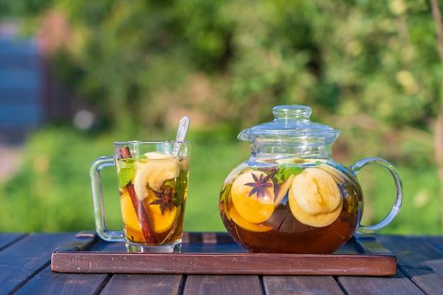 Zdrowa herbata jabłkowa w szklanym dzbanku do herbaty i kubku w letnim ogrodzie na drewnianym stole. ścieśniać