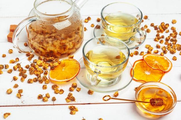 Zdrowa herbata rumiankowa w szklanej filiżance. czajnik, mały słoik miodu