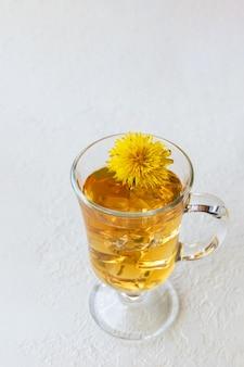Zdrowa herbata ziołowa z mniszka lekarskiego w szklanym kubku, lód i żółty kwiat mniszka wewnątrz na białym tle, widok z góry, kopia przestrzeń, format pionowy. koncepcja zdrowego odżywiania