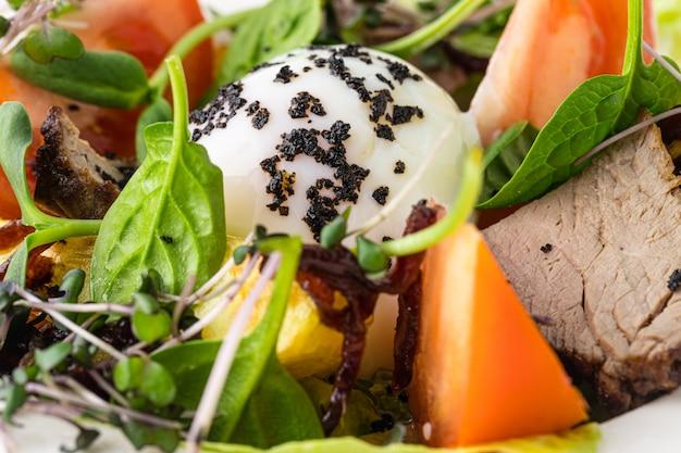 Zdrowa i smaczna sałatka ze świeżych warzyw, ciecierzycy i jajka w koszulce