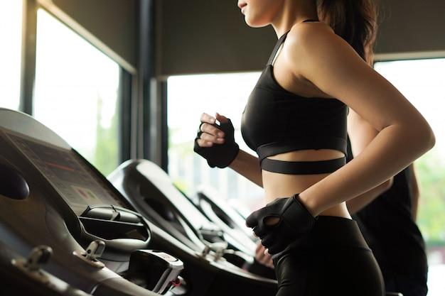 Zdrowa i szczupła kobieta działa lub ćwiczenia na bieżni w siłowni.
