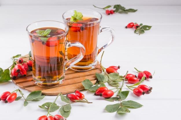 Zdrowa jesienna herbata z psimi różami, gałąź z jagodami na bielu stole.