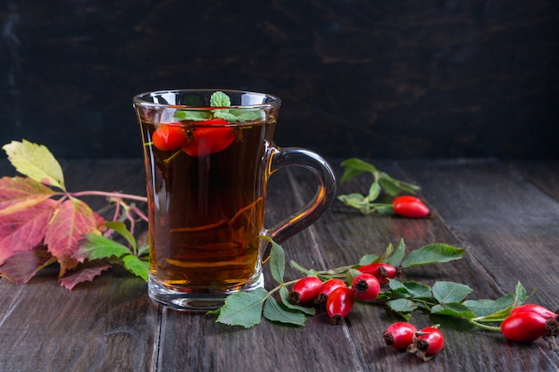 Zdrowa jesienna herbata z psimi różami, gałąź z jagodami na ciemnym stole