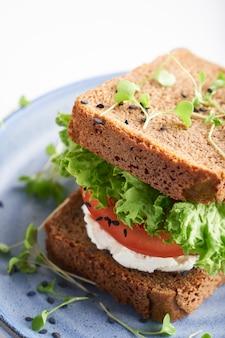 Zdrowa kanapka z bezglutenowym chlebem, pomidorem, sałatą i kiełkującymi mikrograniami, posypana sezamem podana na talerzu