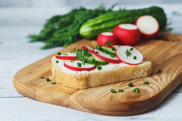 Zdrowa kanapka z rzodkiewką ogórkową i serkiem śmietankowym na drewnianej desce do krojenia