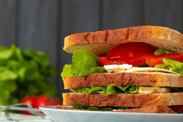 Zdrowa kanapka z warzywami na ciemnym drewnianym tle