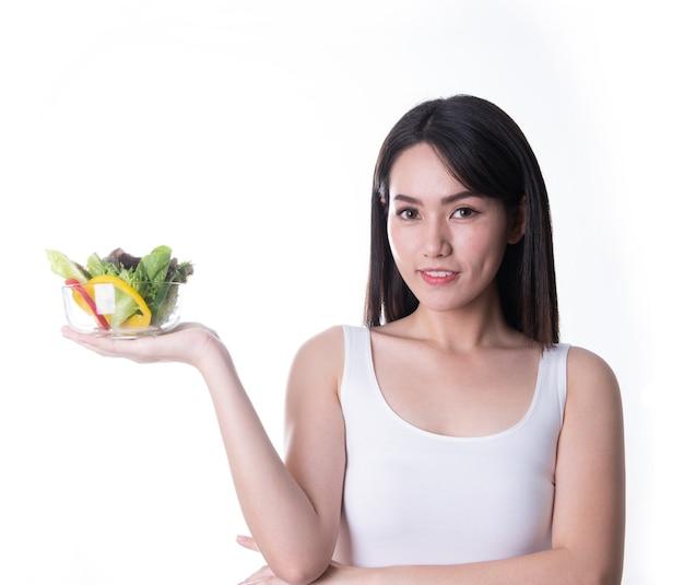 Zdrowa kobieta azji z sałatką na białym tle. zdrowy styl życia wegetariańska zielona żywność.
