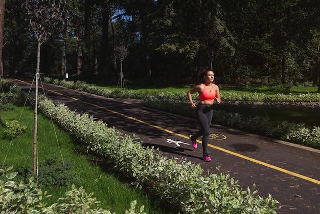 Zdrowa kobieta bieganie bieganie i trening na zewnątrz drogi. koncepcja treningu cardio i utraty wagi