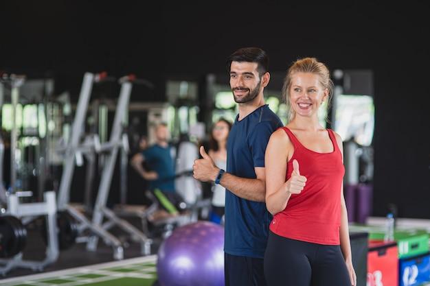 Zdrowa kobieta i mężczyzna śmiejąc się razem na siłowni, fit młoda para treningu