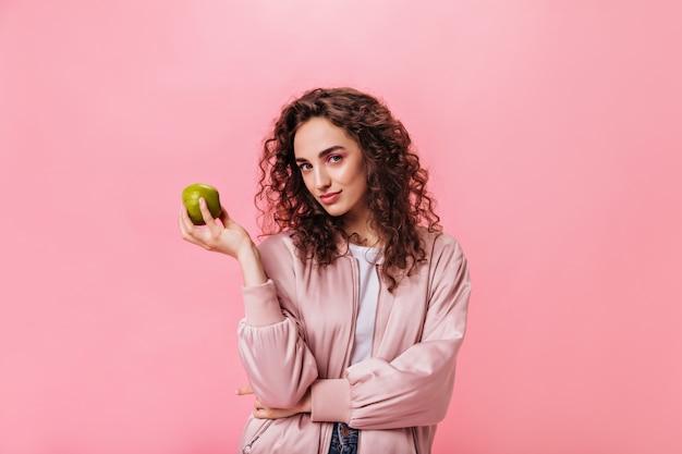 Zdrowa kobieta patrząc w kamerę i trzymając jabłko