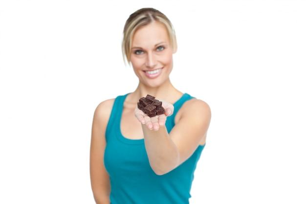 Zdrowa kobieta pokazuje czekoladowego baru kamera przeciw białemu tłu