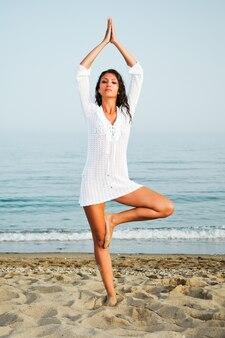 Zdrowa kobieta robi joga na plaży