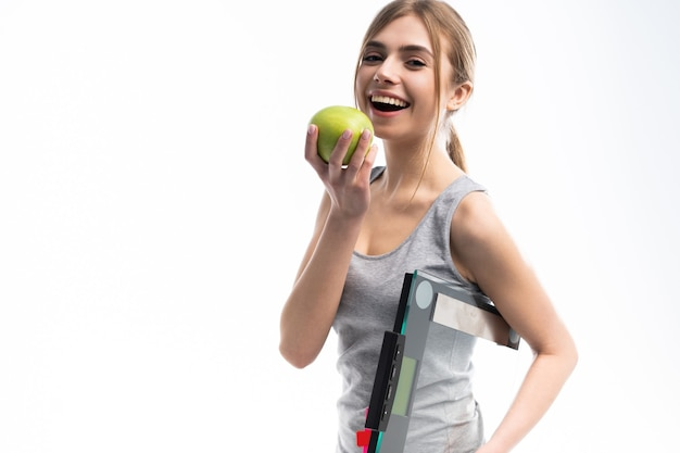Zdrowa kobieta stoi z wagą i zielonym jabłkiem