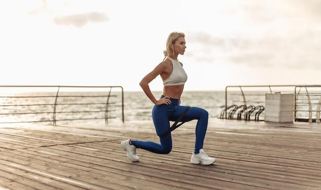 Zdrowa kobieta szkolenia na nadmorskiej promenadzie sportsmenka w sportowej robi rzuca ćwiczenia z gumy fitness na plaży