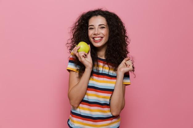 Zdrowa kobieta w wieku 20 lat z kręconymi włosami uśmiechnięta i trzymająca zielone jabłko odizolowane na różowo