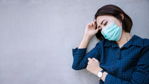 Zdrowa kobieta w zielonej medycznej masce ochronnej pokazuje gest stop. ochrona zdrowia i profilaktyka podczas grypy i epidemii zakaźnej lub covid-19 przy betonowej ścianie