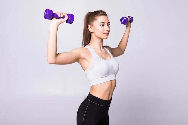 Zdrowa kobieta z hantlami, ćwicząc na białym tle na białej ścianie. koncepcja siłowni fitness