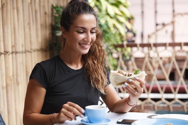 Zdrowa kobieta z opalenizną, siedząc w koszulce na tarasie kawiarni, jedząc śniadanie i pijąc kawę.