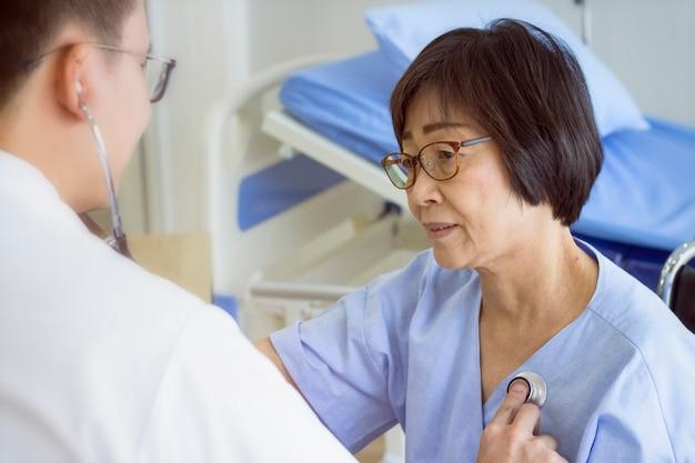 Zdrowa koncepcja; doktorski sprawdza pacjenta serce z stetoskopem przy szpitalem