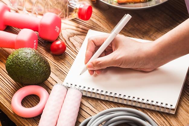 Zdrowa koncepcja z odżywianiem żywności w pudełku na lunch i sprzętem fitness z kobietą, czas pisania, aby odzyskać zdrowie w dzienniku