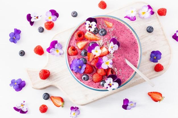 Zdrowa letnia jagodowa miska na smoothie z kwiatami i nasionami chia