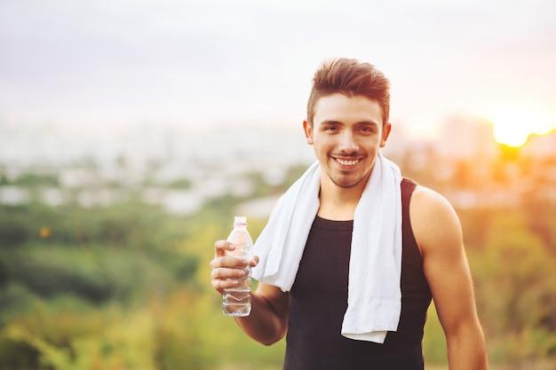 Zdrowa mężczyzna woda pitna na naturze podczas gdy odpoczywający