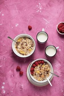 Zdrowa mieszanka muesli z malinami i mlekiem na różowym tle, widok z góry na dół