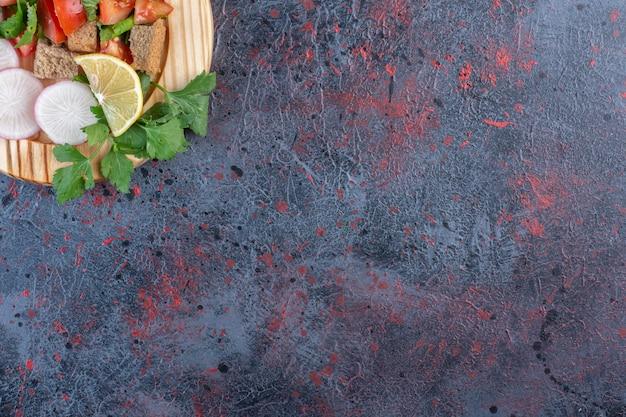 Zdrowa mieszanka warzyw podawana na drewnianym talerzu na czarnym stole.