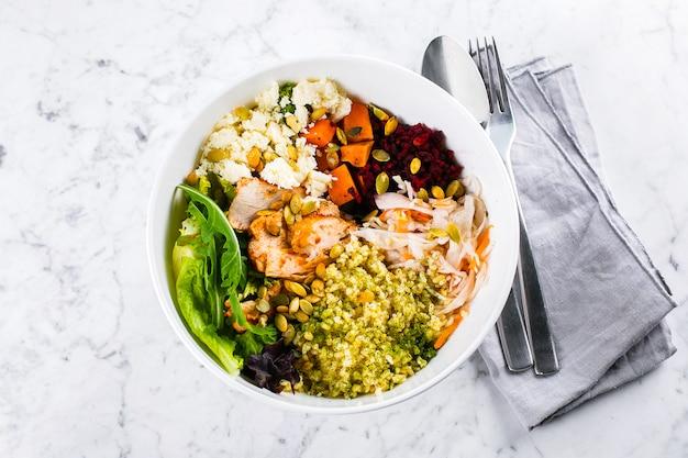Zdrowa miska na lunch. sałatka z mięsem, serem, bulgur i warzywami na marmurze. widok z góry