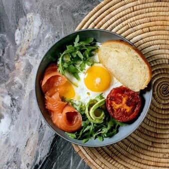Zdrowa miska śniadaniowa z jajkiem sadzonym, łososiem, awokado, grillowanym pomidorem i sałatką z chlebem na słomkowej serwetce na ciemnym marmurowym tle. płaski układanie, kopiowanie przestrzeni
