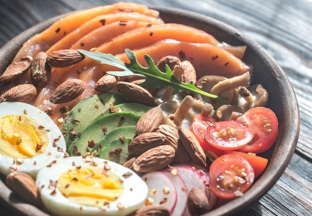 Zdrowa miska z łososiem, awokado, jajkiem i warzywami