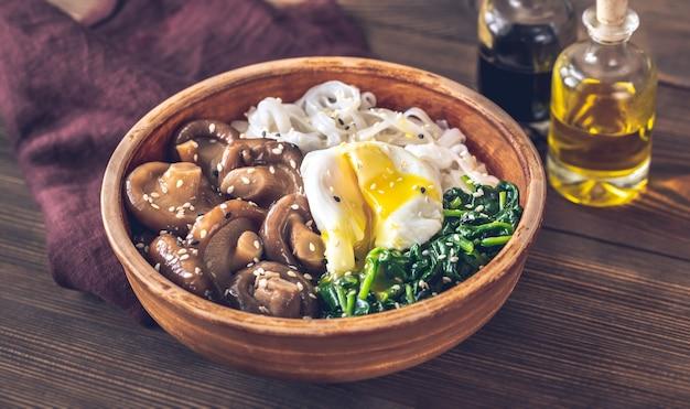 Zdrowa miska z makaronem ryżowym, marynowanym shiitake, jajkiem w koszulce i szpinakiem na parze