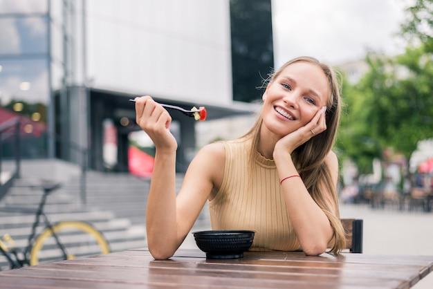 Zdrowa młoda kobieta je sałatkę na świeżym powietrzu w ulicznej kawiarni