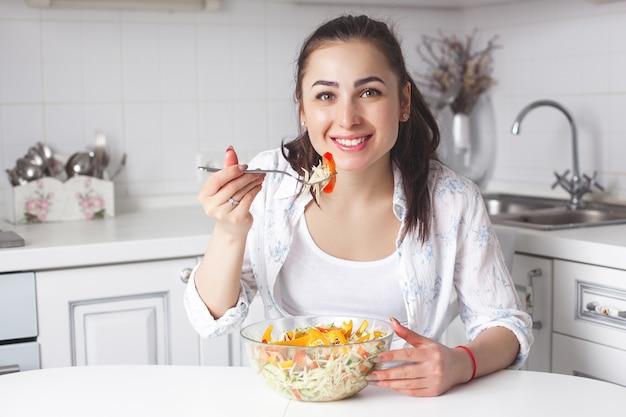 Zdrowa młoda kobieta jedzenie sałatki w kuchni