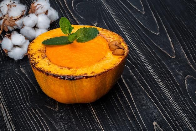 Zdrowa, naturalna zupa krem z dyni na czarnym drewnianym tle