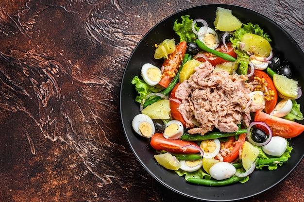Zdrowa, obfita sałatka z tuńczykiem, fasolką szparagową, pomidorami, jajami, ziemniakami i czarnymi oliwkami na talerzu