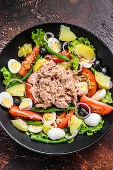 Zdrowa obfita sałatka z tuńczykiem, fasolką szparagową, pomidorami, jajkami, ziemniakami i czarnymi oliwkami w talerzu. ciemne tło.