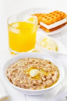 Zdrowa owsianka śniadaniowa z płatkami owsianymi pszennymi, jęczmiennymi i żytnimi i sokiem pomarańczowym