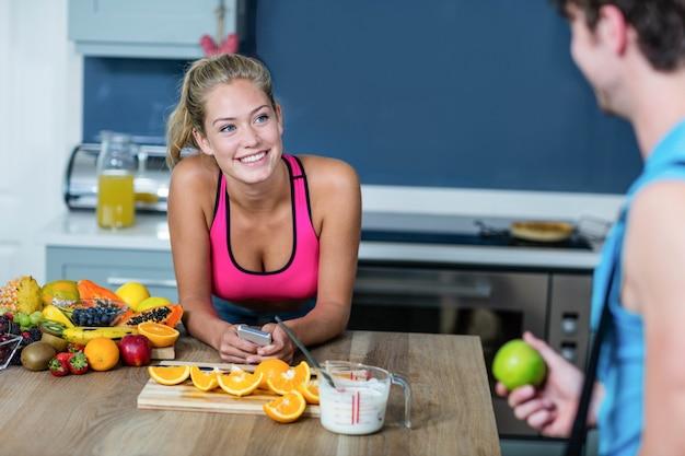 Zdrowa para mówi i trzyma owoc w kuchni