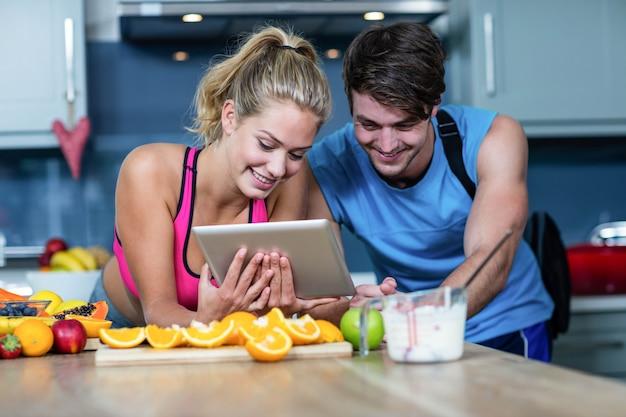 Zdrowa para patrzeje pastylkę w kuchni